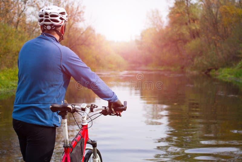 横渡有自行车的年轻运动员岩石地形在他的手上 免版税库存照片