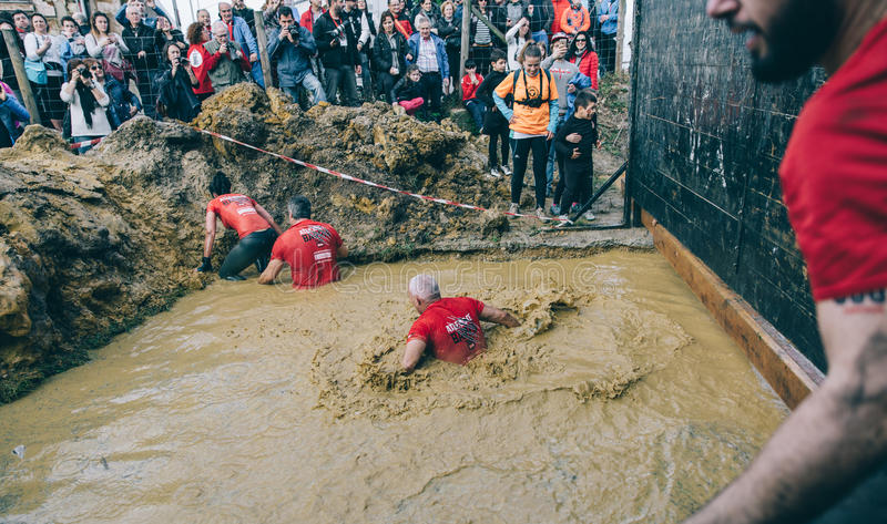 横渡泥的赛跑者在极端越障竞赛测试挖坑  图库摄影