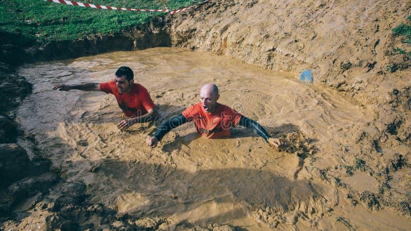横渡泥的赛跑者在极端越障竞赛测试挖坑  库存照片