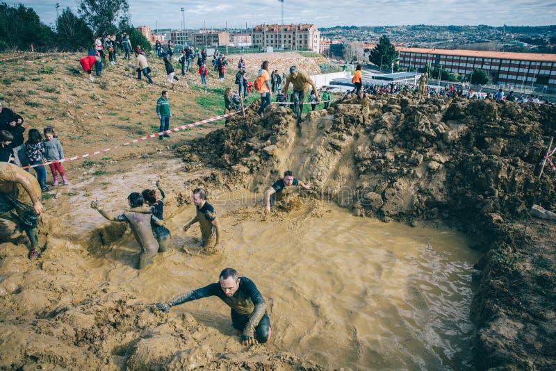 横渡泥的赛跑者在极端越障竞赛测试挖坑  库存图片