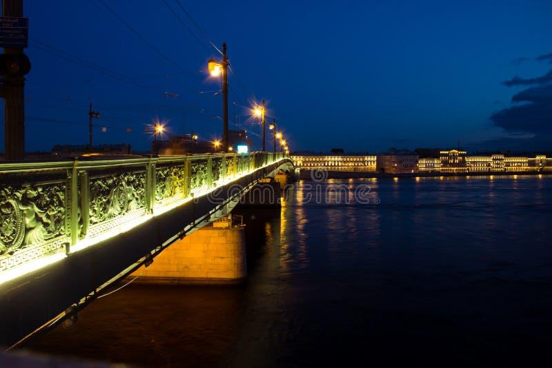 横跨一条宽河的夜桥梁在晚上 库存图片