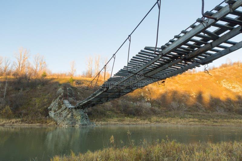 横跨一条小河的非常老垂悬的人行桥 免版税库存照片