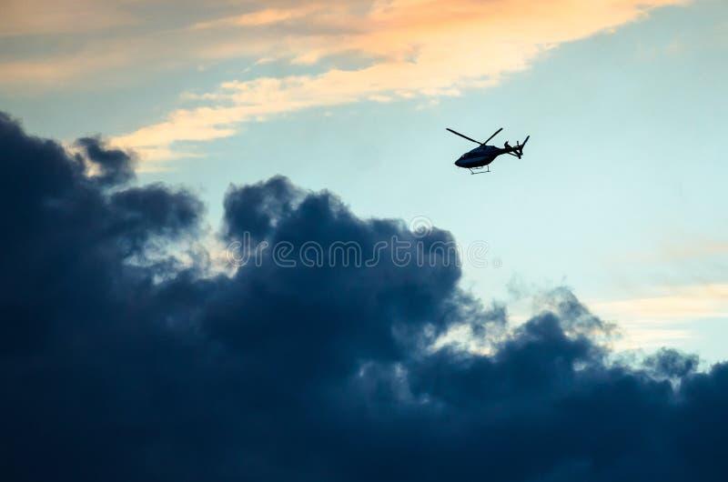 横跨日落天空的现出轮廓的直升机飞行 免版税库存照片