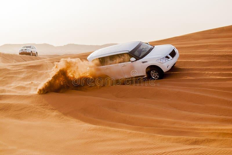横跨沙漠沙丘的SUVs艰苦跋涉 免版税库存图片