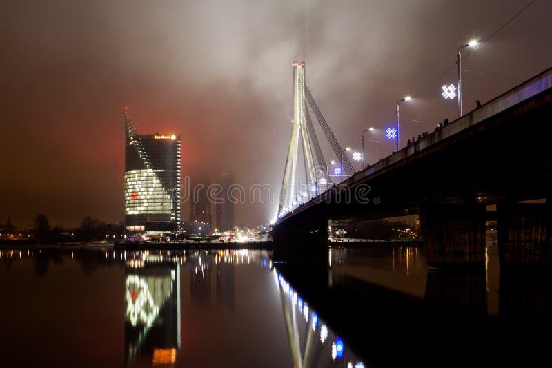 横跨河道加瓦河的一个晚上视图对Vansu桥梁和Swedbank总部 免版税库存图片