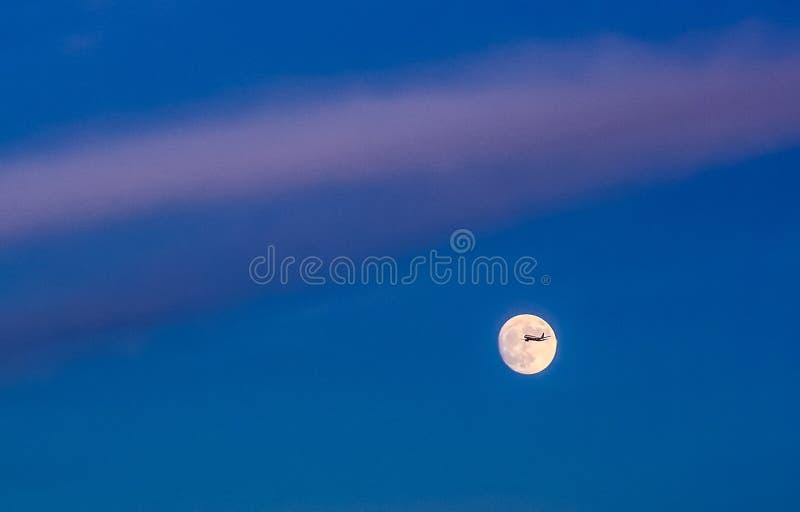 横跨满月的商业喷气机飞行 免版税库存照片