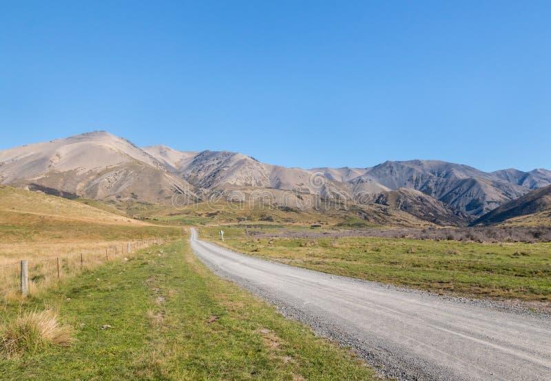 横跨贫瘠小山的乡下公路在Molesworth驻地,新西兰附近的南阿尔卑斯山 库存图片