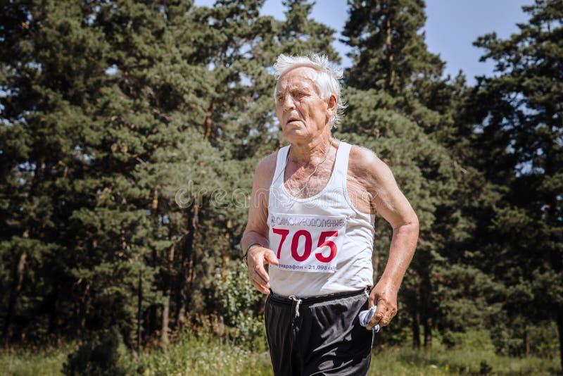 横跨路的老人奔跑在森林里 库存图片