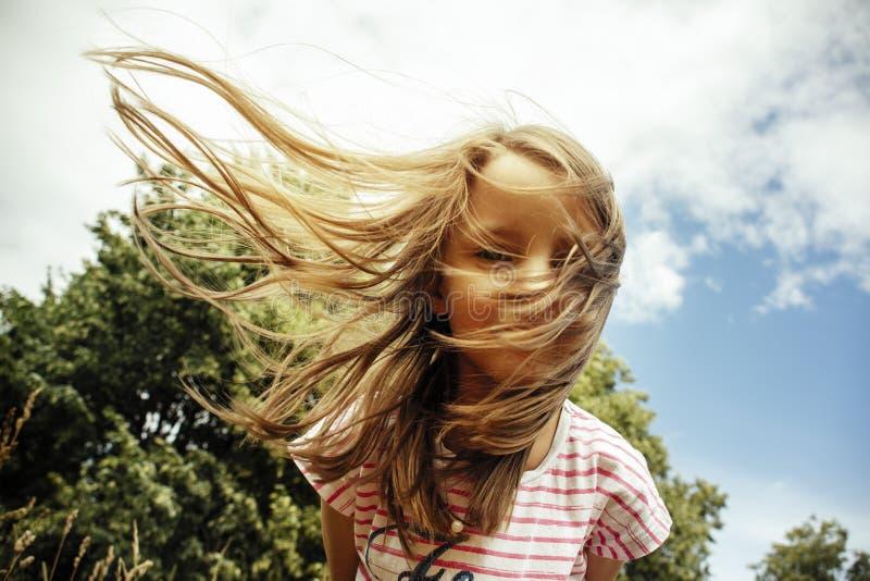 横跨领域的女孩赛跑在日落 免版税图库摄影
