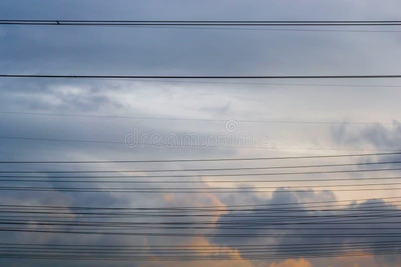 横跨风雨如磐的云彩的多条水平的高压电缆线,在日落 力量/电发行的简单的概念 免版税库存照片