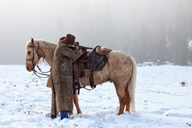 横跨他的马鞍的牛仔射击 库存照片
