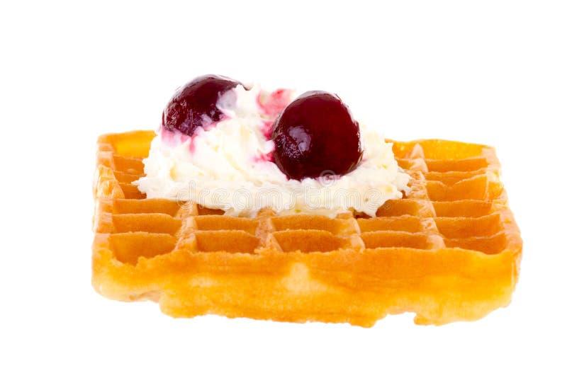 樱桃和打好的奶油在发亮的新近地被烘烤的奶蛋烘饼 免版税库存图片