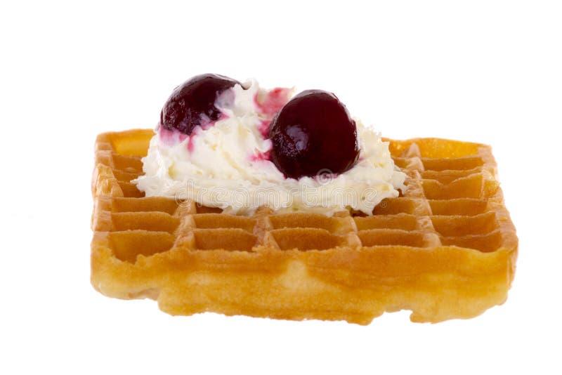 樱桃和打好的奶油在新近地被烘烤的奶蛋烘饼 免版税图库摄影