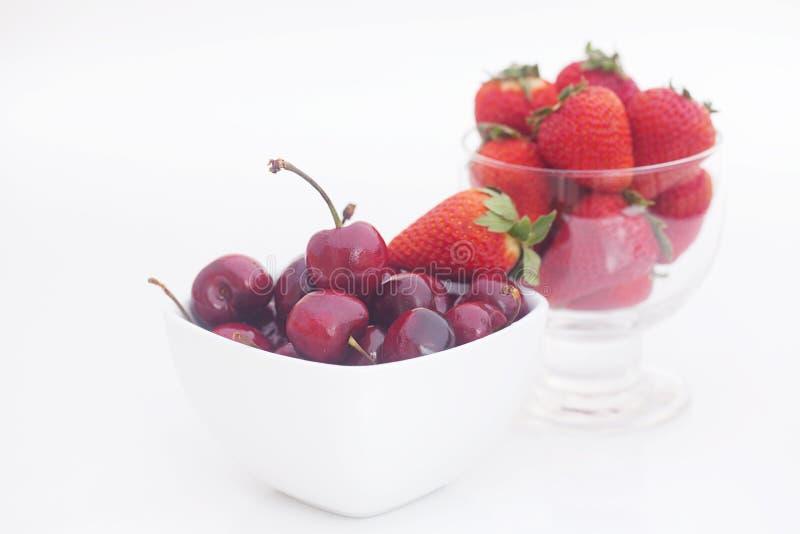 樱桃和草莓在一个陶瓷和玻璃碗 免版税图库摄影