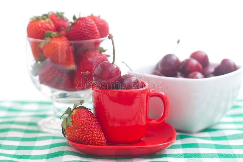 樱桃和草莓在一个陶瓷和玻璃碗 库存照片