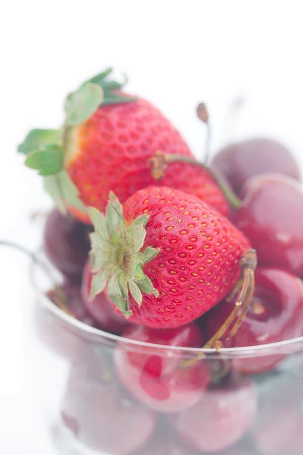 樱桃和草莓在一个玻璃碗 免版税库存图片