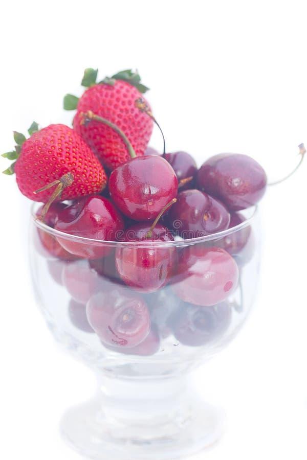 樱桃和草莓在一个玻璃碗 免版税库存照片