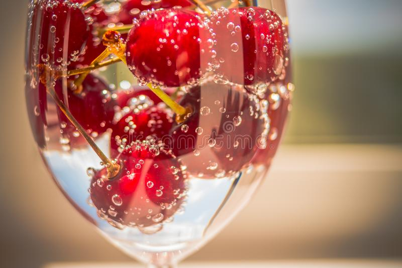 樱桃堆在水中与泡影 与尾巴的樱桃 宏指令 成熟樱桃,在一块玻璃的甜樱桃在苏打 库存图片