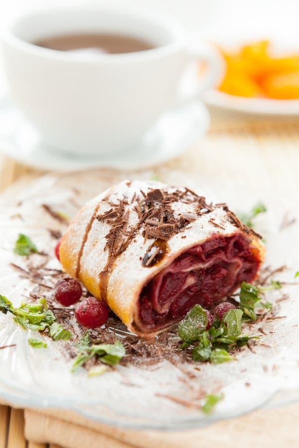 樱桃果馅奶酪卷用巧克力和一杯茶 免版税图库摄影