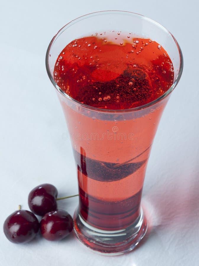 樱桃汁关闭玻璃用樱桃果子和Bubles 库存照片