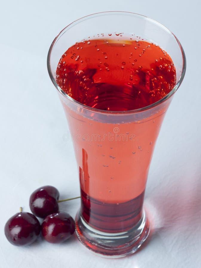 樱桃汁关闭玻璃用樱桃果子和Bubles 免版税库存照片