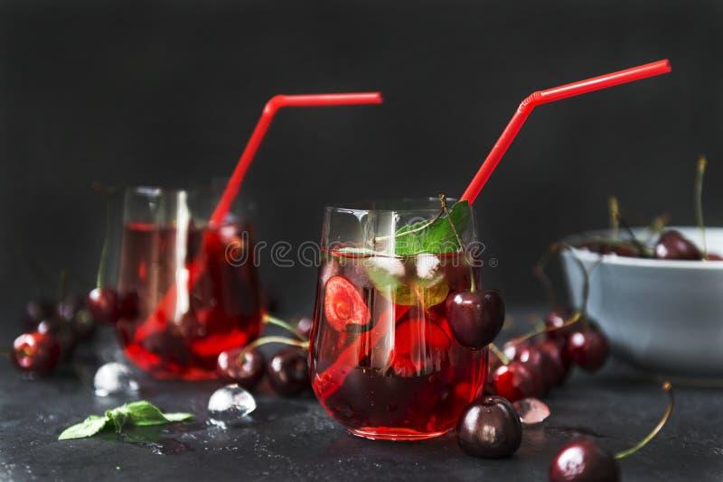 樱桃汁,柠檬水用在一块玻璃的樱桃在黑背景 免版税库存图片