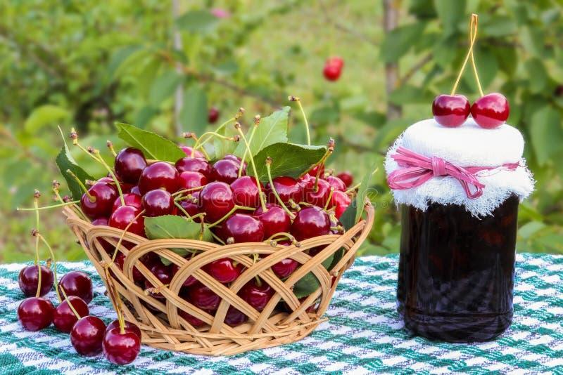 樱桃篮子和樱桃果酱在樱桃树背景刺激  免版税库存照片