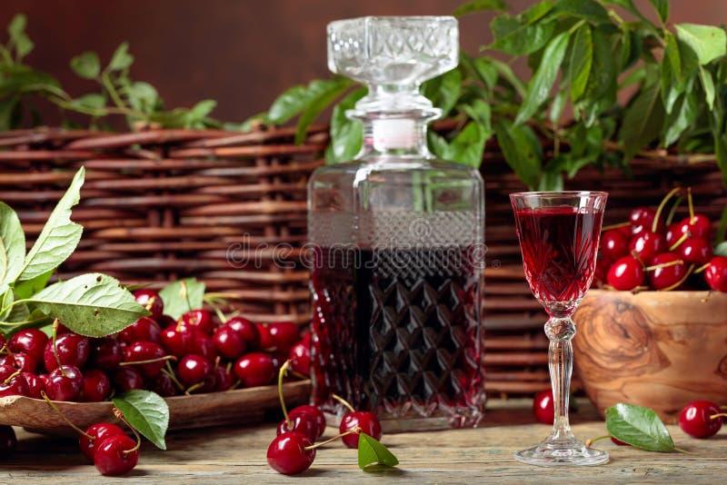 樱桃酒和红色樱桃在一个木碗在一张木桌上在庭院里 免版税图库摄影