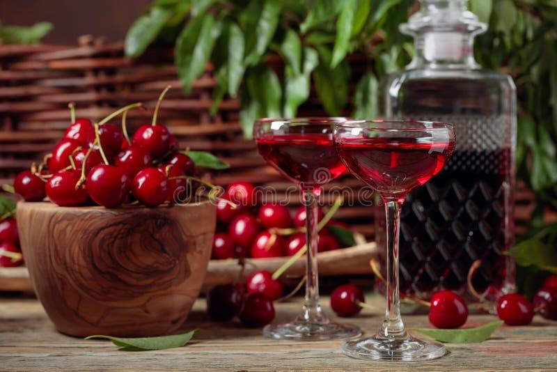 樱桃酒和红色樱桃在一个木碗在一张木桌上在庭院里 库存图片
