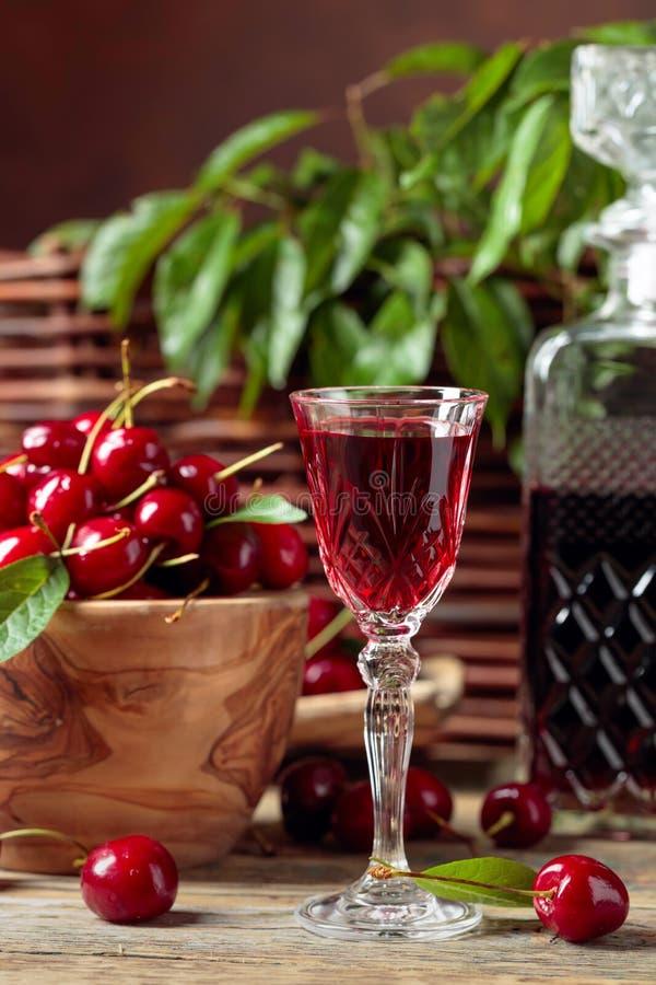 樱桃酒和红色樱桃在一个木碗在一张木桌上在庭院里 免版税库存照片