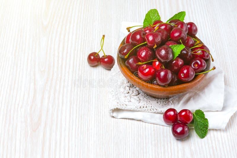 樱桃,在黏土板材的樱桃在桌上 库存照片