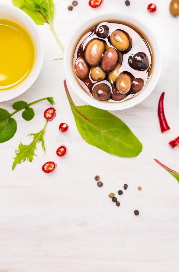 橄榄和油在白色碗用香料和草本在木 免版税库存照片
