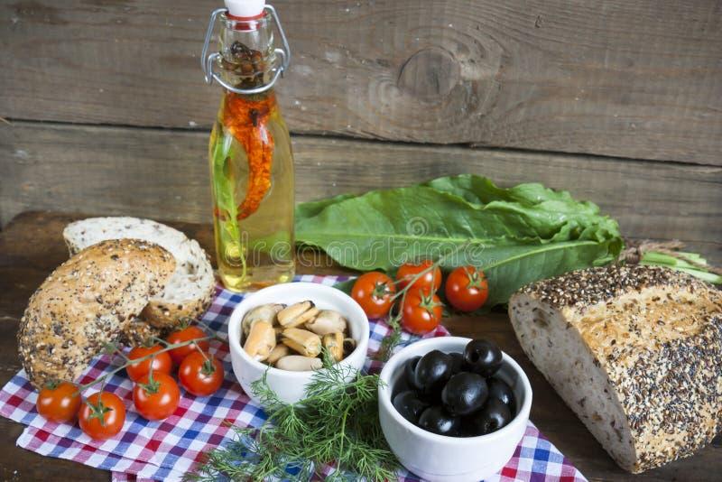 黑橄榄和淡菜在陶瓷碗、新鲜的蕃茄、面包和瓶橄榄油用香料 库存图片
