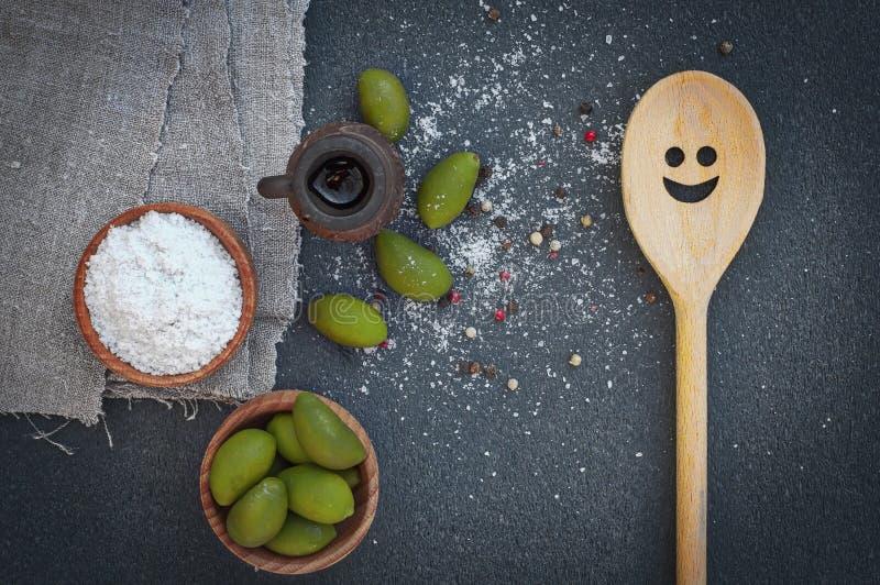 绿橄榄和盐在木碗 库存图片