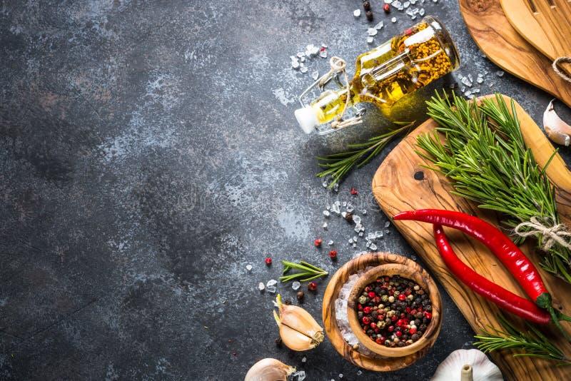 橄榄油、草本和香料在一张黑暗的石桌上 库存图片