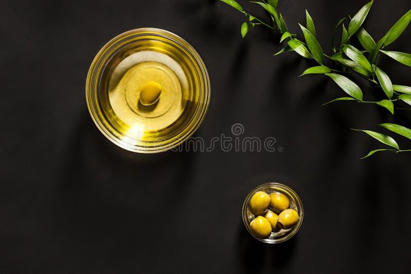 橄榄油和在木表的橄榄树枝 库存照片