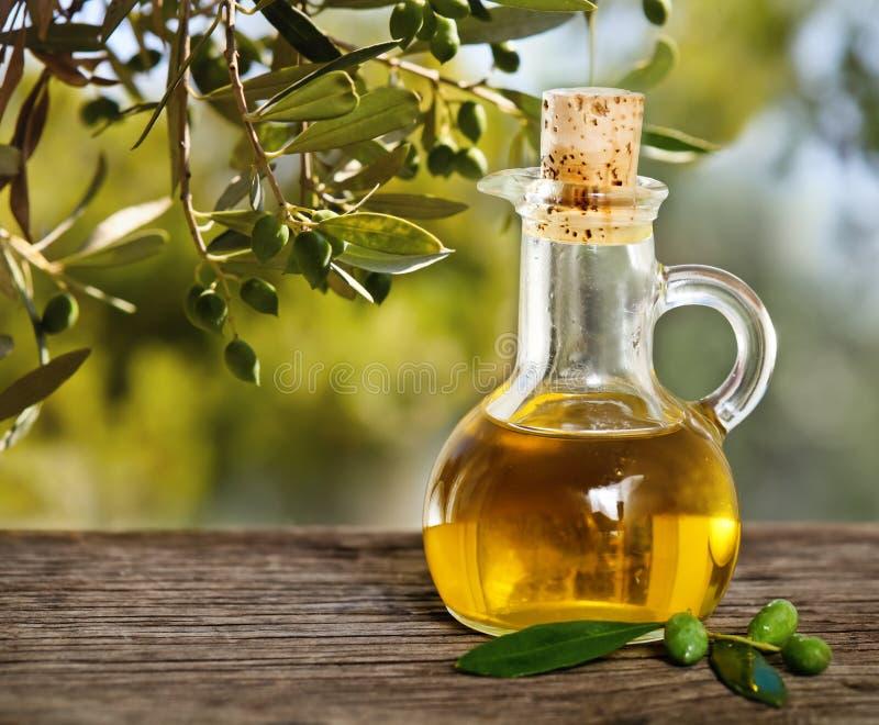 橄榄油和在木表的橄榄树枝 免版税库存照片