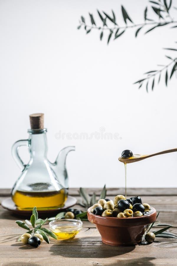橄榄油和橄榄树枝在木桌上 图库摄影