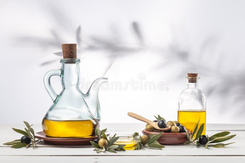 橄榄油和橄榄树枝在木桌上 免版税库存图片