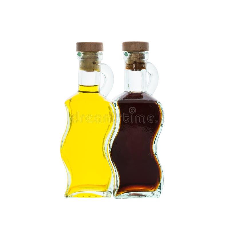橄榄油和醋在玻璃瓶被隔绝在白色 免版税库存图片
