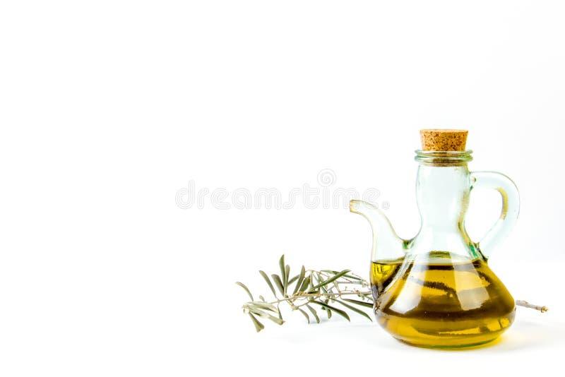 橄榄油有一个橄榄树分支的玻璃瓶 免版税库存照片
