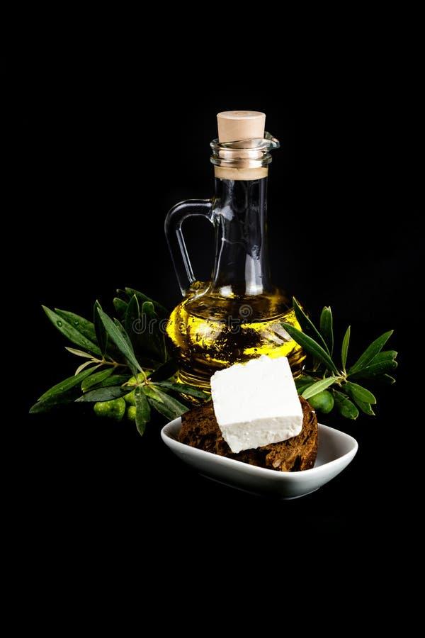 橄榄油瓶、橄榄树枝、乳酪和面包 库存照片