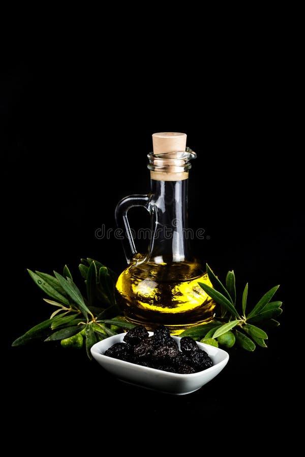 橄榄油瓶、黑橄榄和橄榄树枝 免版税库存照片