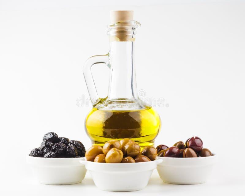 橄榄油瓶和橄榄在碗 免版税库存照片