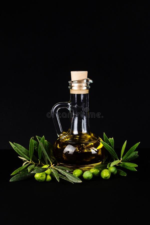 橄榄油瓶和橄榄树枝 库存照片
