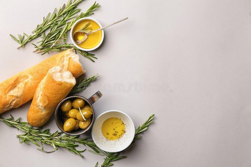 橄榄油用迷迭香和面包在轻的背景 库存照片
