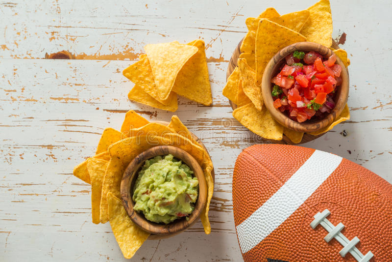 橄榄球党食物,超级杯天,烤干酪辣味玉米片辣调味汁鳄梨调味酱捣碎的鳄梨酱 库存照片
