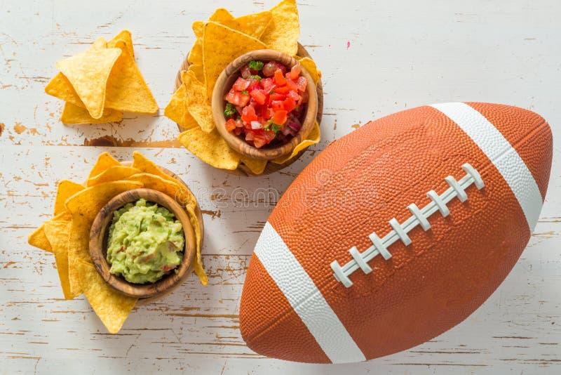 橄榄球党食物,超级杯天,烤干酪辣味玉米片辣调味汁鳄梨调味酱捣碎的鳄梨酱 免版税库存照片