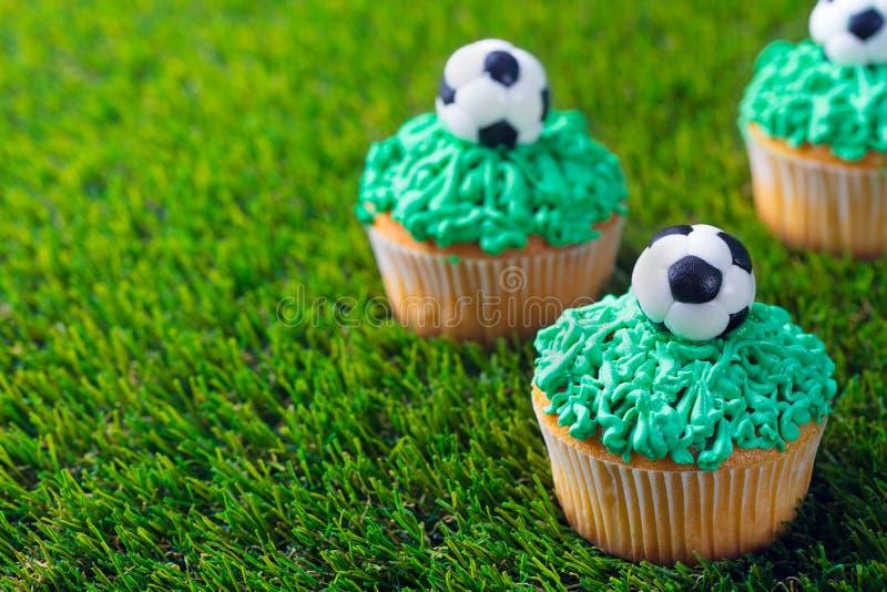 橄榄球党,生日在绿草背景的装饰的杯形蛋糕 r 免版税图库摄影