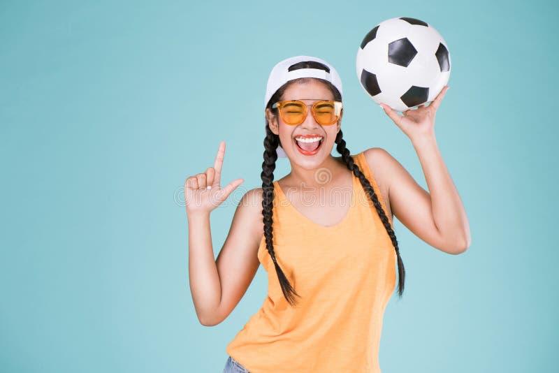 橄榄球冠军逗人喜爱的妇女爱好者  拿着球的适合的女孩 库存照片